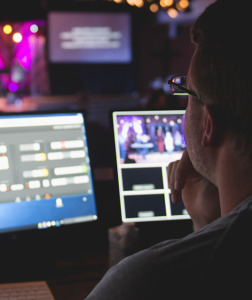 Man handling video equipment at worship service - MinistryTech.com